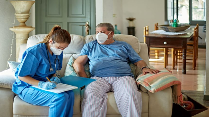 healthcare worker takes notes with masked patient